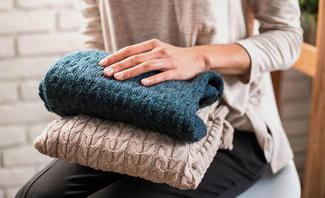 Frau hält Pullover in Hände
