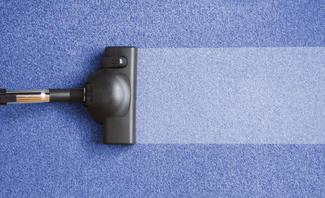 Staubsauger auf blauem Teppich
