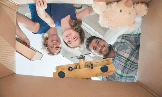 Familie packt Gegenstände in Kiste