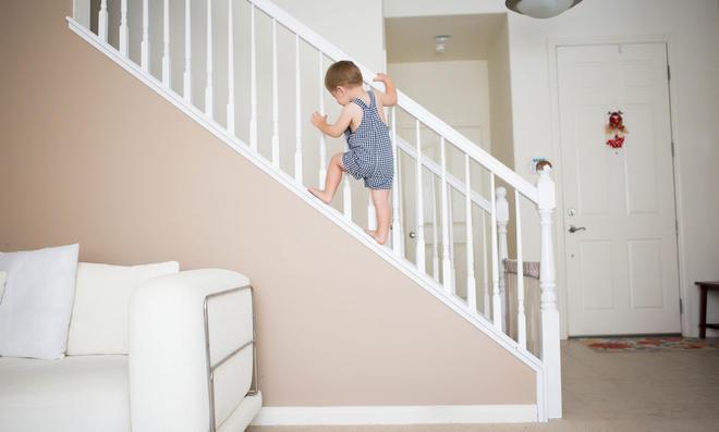 Kleinkind klettert Treppengeländer hoch