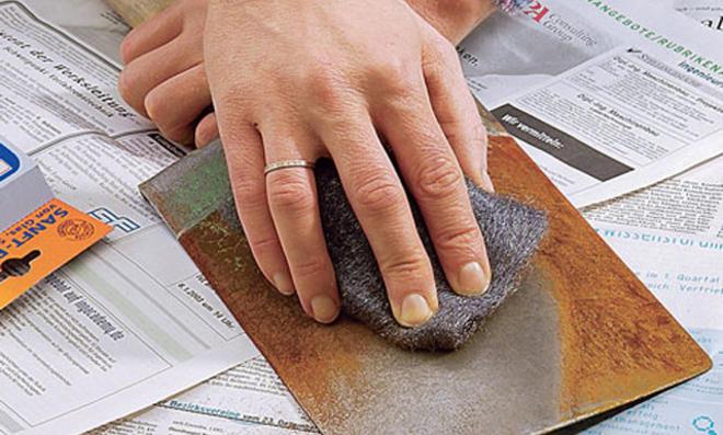 Flugrost von einem Spaten wird mit Stahlwolle entfernt
