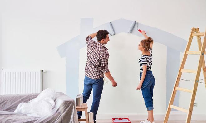 Paar malt Haus an Wand